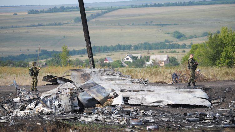 Des enquêteurs sur les lieux du crash du vol MH17 près de Donetsk (Ukraine), le 25 juillet 2014. (SONER KILINC / ANADOLU AGENCY / AFP)