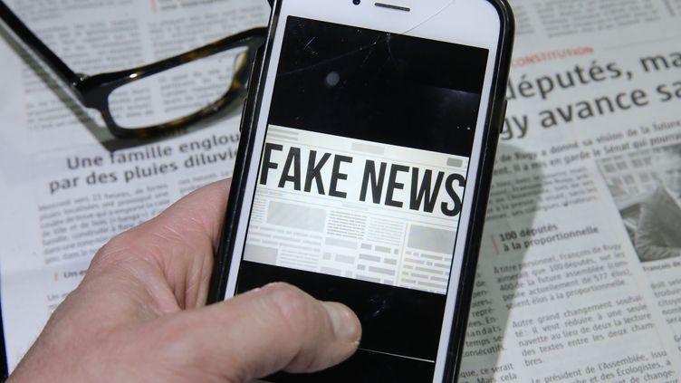 "Un homme avec son téléphone, illustration ""fake news"". (JEAN-FRANCOIS FREY / MAXPPP)"