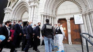 Le président Emmanuel Macron, accompagné de plusieurs personnalités, sur les lieux de l'attaque au couteau à la basilique Notre-Dame de Nice, le 29 octobre 2020. (ERIC GAILLARD / AFP)