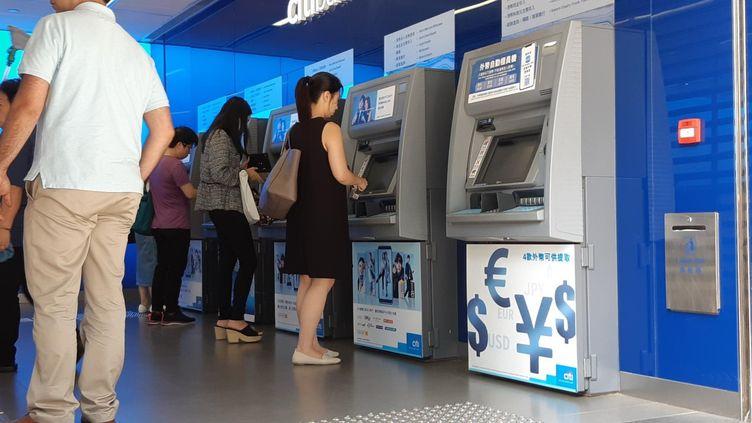 Une femme retire de l'argent à un distributeur à Hong Kong, le 16 août 2019 (JEREMY TUIL / FRANCEINFO)