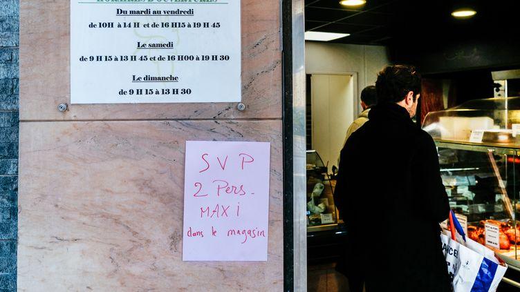 Une affiche sur un magasin limite l'accès à deux personnes maximum, à Paris, le 15 mars 2020. (MATHIEU MENARD / HANS LUCAS)