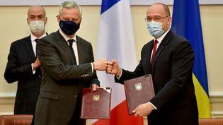 Le Premier ministre ukrainien Denys Shmyhal (à droite) et Bruno Le Maire, ministre français de l'Économie et des Finances (à gauche) signent des accords pour 1,3 milliard d'euros, à Kiev (Ukraine), le 13 mai 2021. (SERGEI SUPINSKY / AFP)