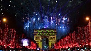 Des badaudsprennent des photos des feux d'artifice qui éclatent dans le ciel de Paris lors des célébrations du Nouvel An sur l'avenue des Champs Elysées, le 1er janvier 2020. (MARTIN BUREAU / AFP)