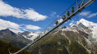 Des visiteurs sur le pont suspendu le plus long du monde, près de Randa, en Suisse, le 29 juillet 2017. (VALENTIN FLAURAUD / AP / SIPA)