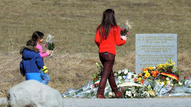 Une femme et deux enfants fleurissant la stèle dressée en hommage aux victimes du crash de l'Airbus de Germanwings au Vernet (Alpes-de-Haute-Provence), le 27 mars 2015. (BORIS HORVAT / AFP)