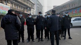 Des agents de sécurité près du marché d'où pourrait provenir le virus, à Wuhan, dans la province du Hubei, en Chine, le 11 janvier 2020. (NOEL CELIS / AFP)