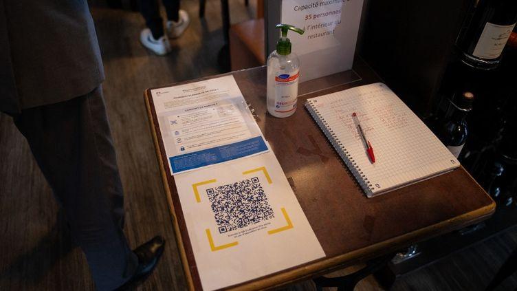 Un QR code côtoie un carnet de rappel version papier, le 26 mai 2021, à Rungis (Val-de-Marne). (ANTOINE DE RAIGNIAC / HANS LUCAS / AFP)