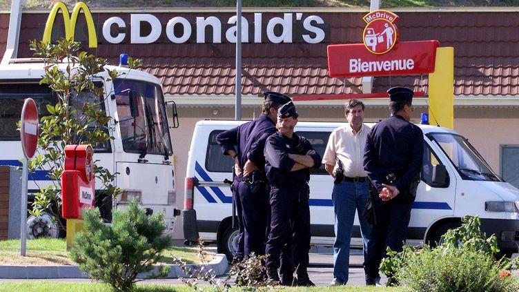 Des forces de l'ordre stationnent devant le restaurant McDonald's de Millau, le 30 juin 2000, avant l'ouverture du procès de José Bové pour le saccage de cet établissement en août 1999. (PHILIPPE DESMAZES / AFP)