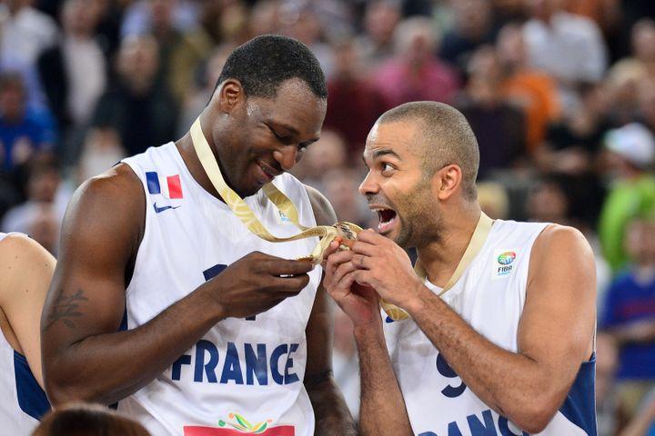 Florent Piétrus et Tony Parker savourent leur médaille d'or, après leur victoire sur la Lituanie, en finale de l'Eurobasket, le 22 septembre 2013 à Ljubljana (Slovénie). (JURE MAKOVEC / AFP)
