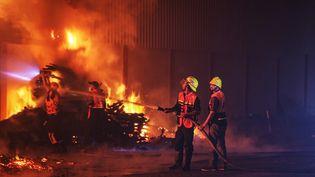 Des pompiers tentent d'éteindre un incendie qui s'est déclaré après que l'artillerie de l'armée israélienne a visé des entrepôts de plastique à l'est de la bande de Gaza, le 20 mai 2021. (ALI JADALLAH / ANADOLU AGENCY / AFP)