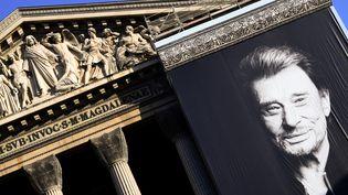Un portrait de Johnny Hallyday, le 9 décembre 2017, devant l'église de la Madeleine à Paris, pour les funérailles du chanteur. (ERIC FEFERBERG / AFP)