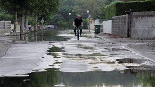 Un homme circule en vélo dans les rues du Cailar (Gard), touché par de fortes précipitations, le 10 septembre 2005. (DOMINIQUE FAGET / AFP)