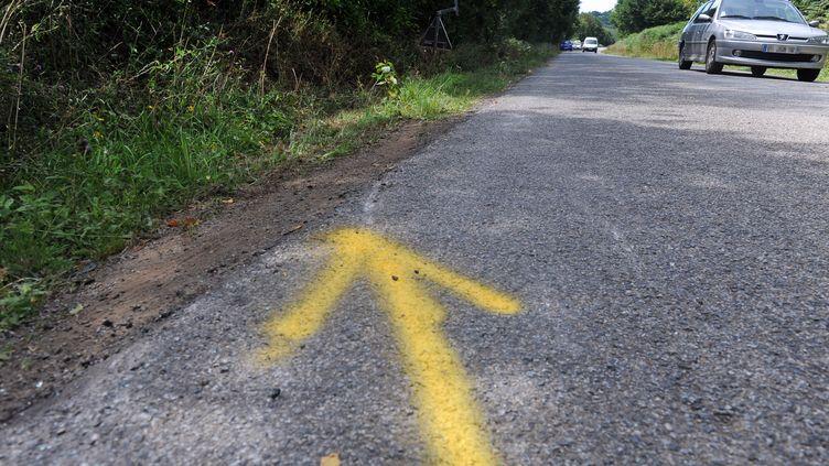 Une flèche laissée par la police pour indiquer la direction dans laquelle allait le véhicule qui s'est retrouvé dans le fossé, faisant 4 morts parmi les 14 personnes à bord, à Rohan (Morbihan), le 2 août 2015. (FRED TANNEAU / AFP)