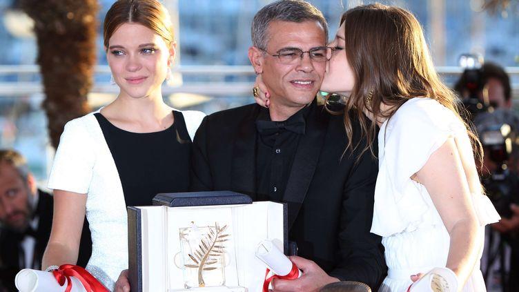 Le cinéaste franco-tunisien Abdellatif Kechiche, entouré de Léa Seydoux (à g.) et Adèle Exarchopoulos (à dr.), le 26 mai 2013 à Cannes. (GAO JING / SIPA)