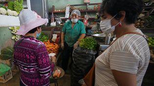 Des femmes portant des masques dans une épicerie de Lima (Pérou), le 2 avril 2020. (CRIS BOURONCLE / AFP)