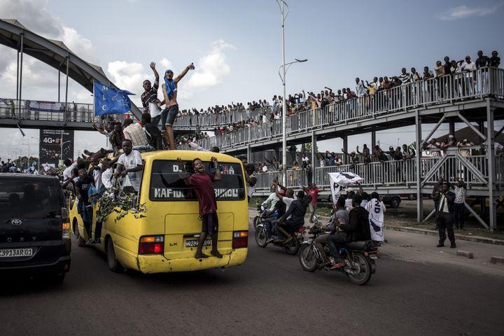 Des partisans du candidat d'opposition MartinFaluyu attendent son arrivée à Kinshasa, sur une route menant à l'aéroport de la capitale, le 21novembre 2018, jour du lancement de sa campagne électorale. (JOHN WESSELS / AFP)