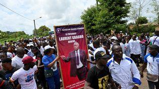 """Rassemblement pour le départ d'une """"caravane de la paix et de la victoire"""", en prélude à l'accueil de Laurent Gbagbo dans sa ville natale de Mama, près de Gagnoa, le 13 juin 2021. Sur l'affiche tenue par des partisans du Front populaire ivoirien (FPI), on peut lire : """"Le président Laurent Gbagbo arrive pour une réconciliation vraie des Ivoiriens."""" (SIA KAMBOU / AFP)"""