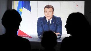Des personnes regardant l'allocution présidentielle d'Emmanuel Macron en direct de l'Elysée mercredi 31 mars 2021. (NICOLAS TUCAT / AFP)