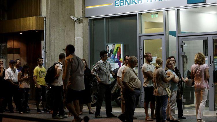 Jusqu'à tard dans la nuit, dimanche 28 juin, les Grecs ont fait la queue devant les banques pour tenter de retirer leurs économies. Depuis lundi, les retraits sont limités à 60 euros par jour. (PANAYIOTIS TZAMAROS / NURPHOTO / AFP)