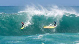 Le surfeur professionnel Ramon Navarro surfe sur la vague tandis que l'autre surfeur, également professionnel, Jamie Mitchell perd le contrôle à Waimea, Hawaï (Etats-Unis). (DARRYL OUMI / GETTY IMAGES NORTH AMERICA / AFP)