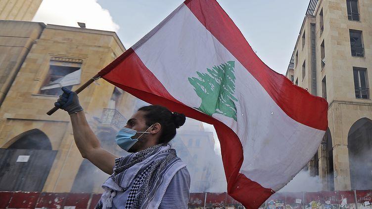 Un manifestant libanais brandissant le drapeau de son pays à Beyrouth, le lundi 10 août 2020. (JOSEPH EID / AFP)