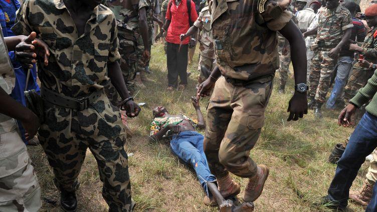 Des soldats centrafricains lynchent un homme accusé d'être un ancien rebelle de la Séléka, le 5 février 2014. (ISSOUF SANOGO / AFP)