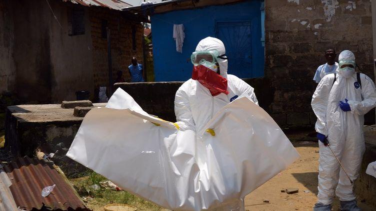 Des travailleurs de la Croix-Rouge évacuent le corps d'un bébé de 18 mois victime de l'épidémie d'Ebola, le 12 septembre 2014 à Monrovia (Liberia). (ZOOM DOSSO / AFP)