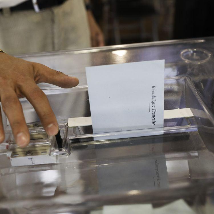 Une enveloppe est placée dans l'urne d'un bureau de vote de Lille, le 11 juin 2017, pour le premier tour des élections législatives. (CITIZENSIDE/THIERRY THOREL / AFP)