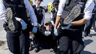 Un militant écologiste arrêté par la police alors qu'il bloquait le pont de Waterloo à Londres, le 20 avril 2019. (NIKLAS HALLE'N / AFP)