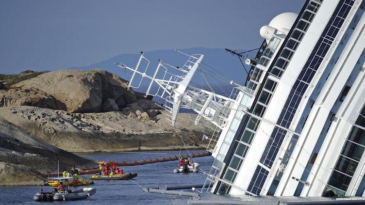 """Des techniciens travaillent sur l'épave du """"Concordia"""", le 26 janvier 2012, sur la côte de l'île italienne du Giglio. (FILIPPO MONTEFORTE / AFP)"""