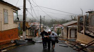 Des sauveteurs aident des habitants à Guayama, à Porto Rico, le 20 septembre 2017. (CARLOS GARCIA RAWLINS / REUTERS)