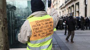 """Les gilets des """"Gilets jaunes"""" se sont transformés en banderoles et porte-étendards. Ici : démissionne Macron, tu fas chier, rends les clés de l'Elysée, tu n'es pas de taille pour gouverner"""". (ZAKARIA ABDELKAFI / AFP)"""