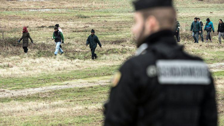 Un policier français surveille des migrants aux abords du tunnel sous la Manche, le 3 décembre 2015 à Coquelles (Pas-de-Calais). (PHILIPPE HUGUEN / AFP)