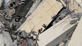 Des secouristes italiens recherchent des victimes dans les décombres du pont autoroutier de Gênes, en Italie, après son effondrement, le 14 août 2018. (VALERY HACHE / AFP)