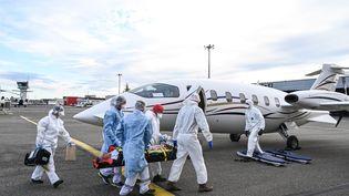 Des patients sont pris en charge à Bron, près de Lyon (Rhône) pour être transférés vers un autre hôpital, le 27 octobre 2020. (PHILIPPE DESMAZES / AFP)
