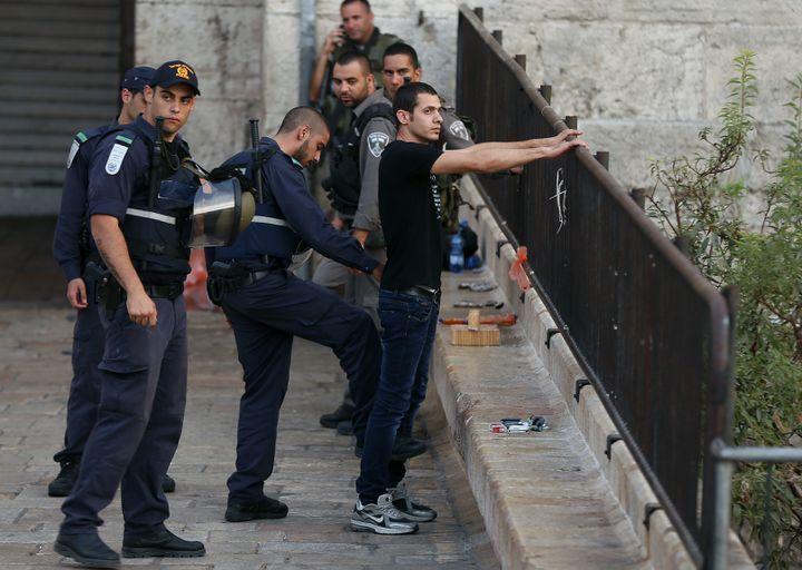 Des policiers israéliens contrôlent un homme dans Jérusalem-Est, mardi 13 octobre 2015. (AHMAD GHARABLI / AFP)
