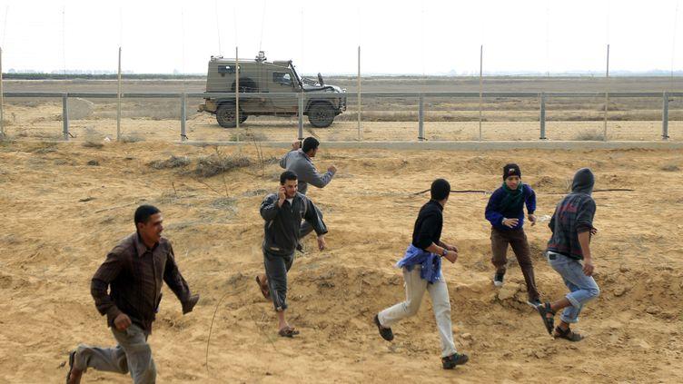 De jeunes Palestiniens fuient à l'approche d'un véhicule de l'armée israélienne le long de la clôture qui marque la frontière entre la bande de Gaza et Israel, le 23 novembre 2012. (SAID KHATIB / AFP)