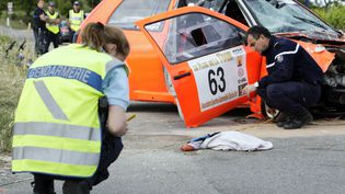 Pompiers et gendarmes s'affairent autour de la voiture de rallye accidentée dont la sortie de route a fait deux morts et quinze blessés à Plan-de-la-Tour (Var), le 19 mai 2012. (JEAN-CHRISTOPHE MAGNENET / AFP)