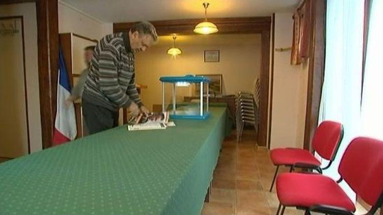 Le maire d'Ecollemont (Marne) et son adjoint installent le bureau de vote pour le premier tour de la présidentielle, le 20 avril 2012. (FTVI / FRANCE 3)