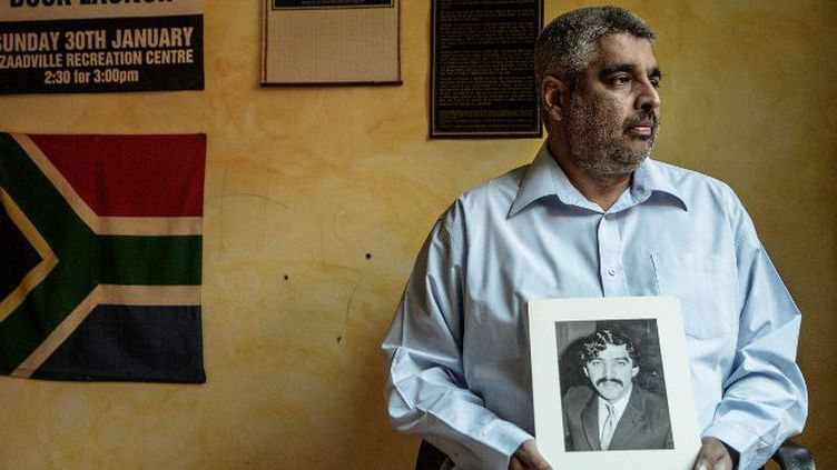 Imtiaz Cajee, neveu d'Ahmed Timol, avec une photo de son oncle, mort en octobre 1971 pendant le régime de l'apartheid. C'est en grande partie grâce à lui que l'enquête concernant ce décès suspect a pu être relancée. Photo prise le 25 mai 2017 à Prétoria. (AFP - GIANLUIGI GUERCIA)