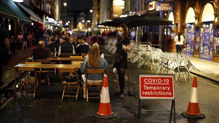 Une rue de Londres, avec pubs et restaurants. Ces établissementsdoivent désormais fermer à 22h, une décision du gouvernement pour freiner le Covid-19. (TOLGA AKMEN / AFP)