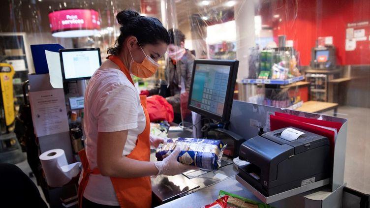 Une caissière travaille à son poste avec des gants et un masque en pleine épidémie de Covid-19, le 8 avril 2020, à Paris. (illustration) (THOMAS SAMSON / AFP)