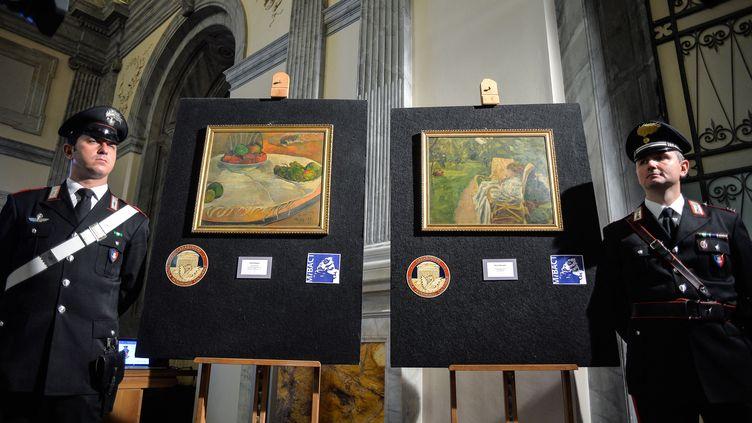 """Des carabiniers italiens encadrent les deux tableaux volés à Londres en 1970 et découverts en Italie, """"Fruits sur une table ou nature morte au petit chien"""" de Gauguin et""""La femme aux deux fauteuils"""" de Bonnard, le 2 avril 2014 (ANDREAS SOLARO / AFP)"""