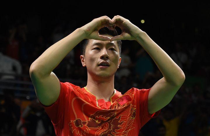 Le Chinois Ma Long forme un cœur avec ses doigts après avoir battu son compatrioteZhang Jike en finale du tennis de table aux JO de Rio (Brésil) le 11 août 2016. (JIM WATSON / AFP)