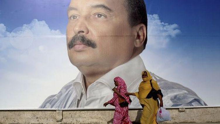 Des femmes passent à côté d'une affiche du président mauritanien sortant,Mohamed Ould Abdel Aziz, le 18 juin à Nouakchott, capitale de la Mauritanie. (Reuters - Joe Penney)
