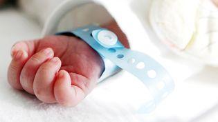 Un nourrisson dort dans son couffin, le poignet entouré d'une étiquette à son nom, le 21 janvier 2013. (VLADIMIR NENOV / EYEEM / GETTY IMAGES)