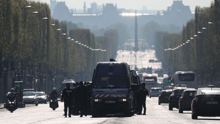 """Les forces de l'ordre stationnent sur les Champs-Elysées, le 6 avril 2019, en prévision d'une mobilisation des """"gilets jaunes"""". (KENZO TRIBOUILLARD / AFP)"""
