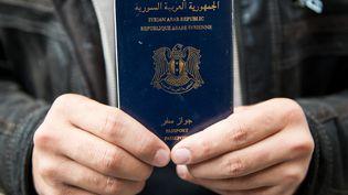 Un homme tenant un passeport syrien à Lübeck (Allemagne), le 8 septembre 2015. (DANIEL REINHARDT / AFP)