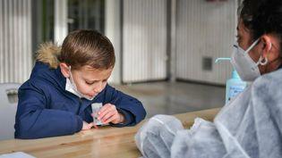 Un élève en école élémentaire effectue un test salivaire Covid-19 en crachant dans un tube à essai, à l'école primaire de La Foret à Eysines (Nouvelle-Aquitaine), le 25 février 2021. (UGO AMEZ/SIPA)
