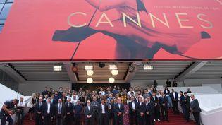 En mémoire des victimes de l'attentat de Manchester, le maire de Cannes David Lisnard, les responsables du festival de Cannes, ainsique plusieurs acteurs et membres de l'organisation ont observé une minute de silence, le 24 mai 2017, sur les marches du palais. (ANNE-CHRISTINE POUJOULAT / AFP)
